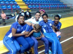 Integrantes del equipo femenino del Zulia en un banco en el gimnasio sede del evento.