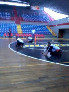 Tres de los integrantes de uno de los equipos masculinos del Zulia en la cancha de juego durante uno de los encuentros del torneo, con sus uniformes negro y azul.