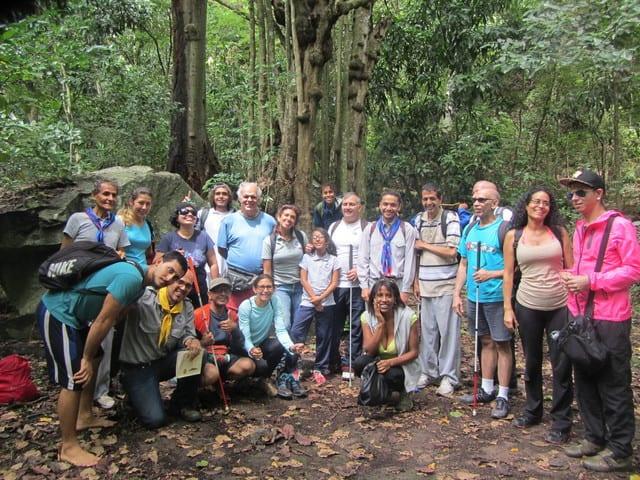 Grupo de PCD visual con sus guías (20 personas), todos muy sonrrientes, en el camino a Quebrada Quintero, con grandes árboles y rocas de fondo, durante la segunda caminata al Ávila.