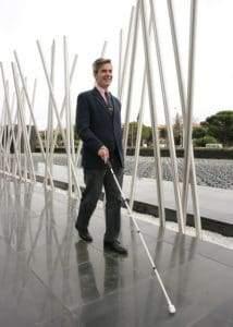 Persona ciega paseando con su bastón (foto de la ONCE).