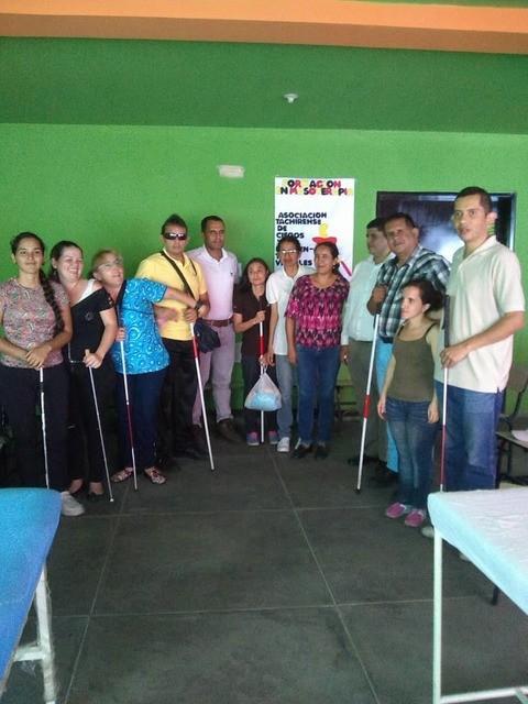 Participantes del curso de masoterapia de ATCIDEV, de pie, con sus bastones.