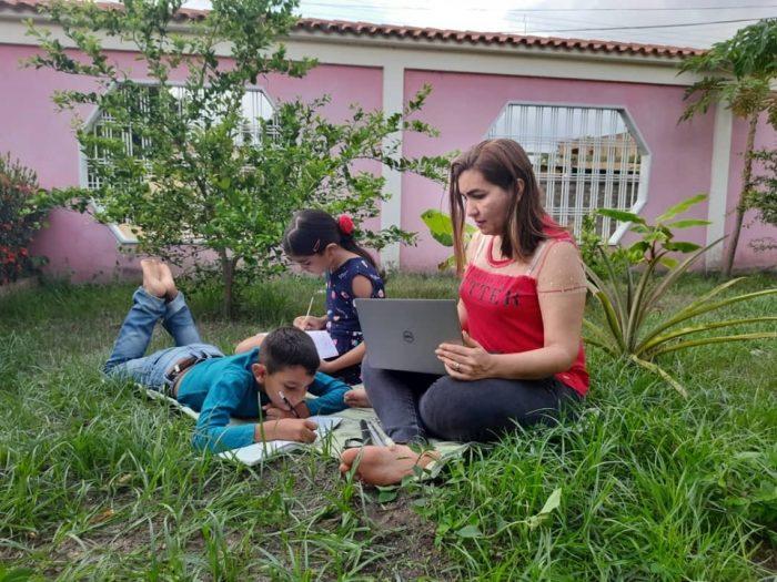 Celeste Fajardo con una laptop y sus 2 hijos realizando tareas educativas.